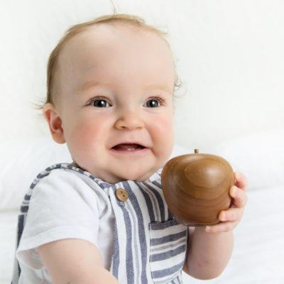 Baby holding wooden apple