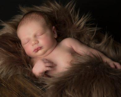 newborn baby asleep on brown faux fur