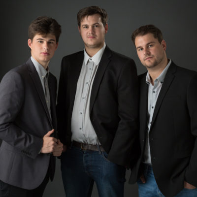 Three male siblings in dark suits