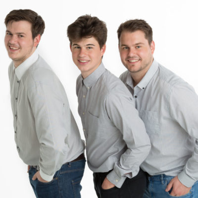 Three male siblings on white background