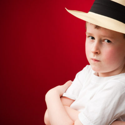 Young boy wearing a panama hat and serious expression