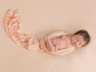 Newborn baby wrapped in peach fabric