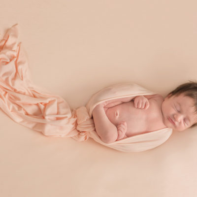 Newborn baby wrapped in peach fabric