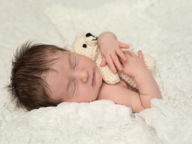 Newborn with dark hair holding teddy