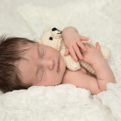 Newborn with dark hair holding teddy