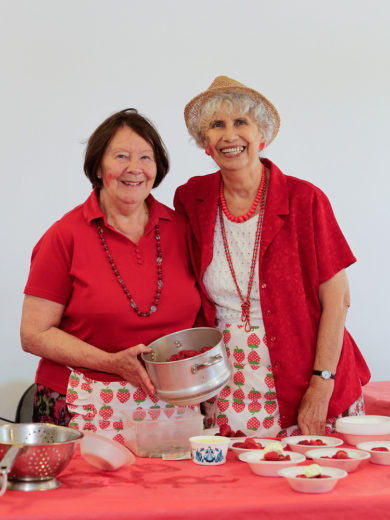 Two ladies serving strawberries and cream