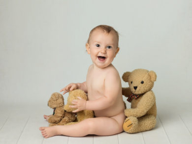 laughing baby with teddies