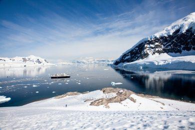 view from antarctic peninsula towards ship in the ocean
