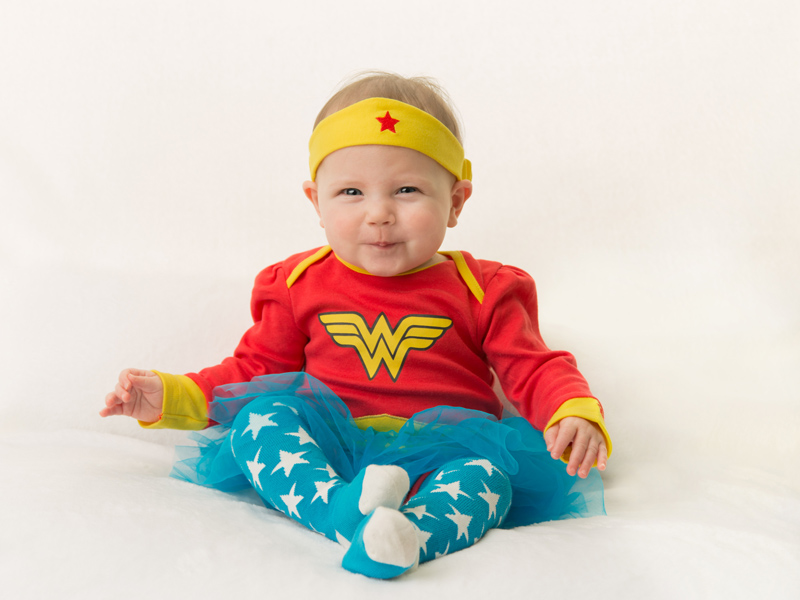 Smiling baby in Wonder Woman costume